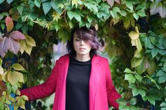 Portrait of a beautiful girl in a red coat. In an autumn park Royalty Free Stock Image
