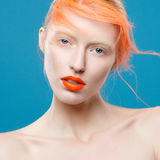 Portrait of beautiful girl with red hair and colorful makeup royalty free stock image