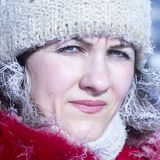 Portrait of a beautiful girl in a red jacket and a white knitted cap in the winter in the frost. Hoarfrost on hair and eyelashes. stock photo