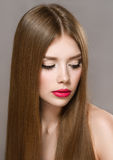 Portrait of beautiful girl with red lips and long hair. Portrait of beautiful girl with red lips and straight long hair. Concept of beauty Royalty Free Stock Images