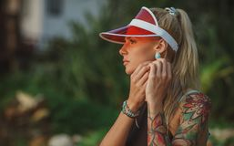 Portrait of a beautiful girl in a red visor closeup. Corrects large earrings. Holiday in Thailand.  Royalty Free Stock Photo