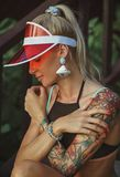 Portrait of a beautiful girl in a red visor closeup. Wearing Large turquoise earrings. Holiday in Thailand.  Stock Photo