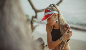 Portrait of a beautiful girl in a red visor closeup. Wearing Large turquoise earrings. Holiday in Thailand On the. Background of evening beach Stock Image