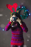 Portrait of beautiful girl with reindeer horns making photos on background of Christmas decorations.  Stock Photography