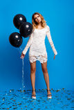 Portrait of beautiful girl resting at party over blue background. Portrait of young beautiful blonde girl in dress looking at camera, holding baloons, resting Royalty Free Stock Photo
