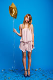 Portrait of beautiful girl resting at party over blue background. Portrait of young beautiful girl in dress holding baloon,  resting at party over blue Royalty Free Stock Photography