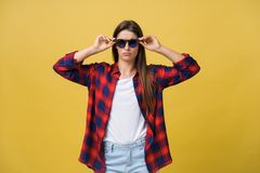 Portrait of a beautiful girl in round glasses on a yellow background in the studio. Portrait of a beautiful girl in round glasses on a yellow background in the royalty free stock photos