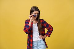 Portrait of a beautiful girl in round glasses on a yellow background in the studio. Portrait of a beautiful girl in round glasses on a yellow background in the royalty free stock photography