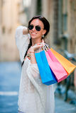 Portrait of beautiful girl with shopping bags on narrow street in Europe. Stock Image