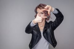 Portrait of beautiful girl with short hairstyle and makeup in casual style black leather jacket standing with cropping composition stock photo