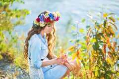 Portrait of a beautiful girl sitting in autumn day. Portrait of a beautiful girl sitting on a lake background in autumn Stock Photo