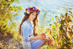Portrait of a beautiful girl sitting in autumn. Portrait of a beautiful girl sitting on a lake background in autumn. Her eyes is closed Royalty Free Stock Photo