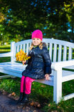 Portrait of beautiful girl sitting on the bench with maple leave Royalty Free Stock Photo