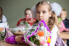 Portrait of beautiful girl sitting at a desk. With a bouquet of flowers stock photography
