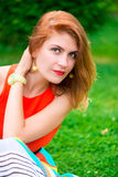 Portrait of a beautiful girl sitting on the grass Stock Photos