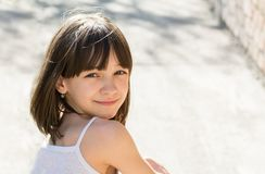 Portrait of a beautiful girl sitting with her back and turning around smiling, Royalty Free Stock Photo