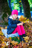 Portrait of beautiful girl sitting with maple leaves in autumn p Stock Photo