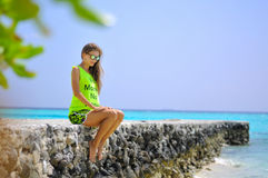 Portrait of a beautiful girl sitting on the pier at the tropical beach Royalty Free Stock Photography