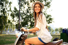 Portrait of a beautiful girl sitting on silver retro scooter, smiling and looking at the camera Stock Photos