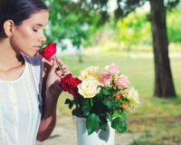 Portrait of beautiful girl smelling homegrown roses in vase Stock Images