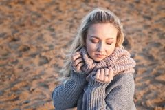 Portrait of beautiful girl smiling with closed eyes and holding scarf on beach royalty free stock image