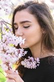 Portrait of beautiful girl sniffs flowering branch. Portrait of beautiful girl with closed eyes sniffs flowering branch of tree stock image