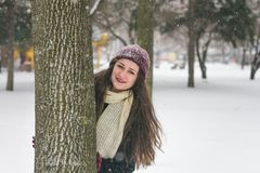Portrait of beautiful girl in the snow hiding behind a tree. Teenage Model Girl having fun in winter park Royalty Free Stock Photo