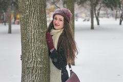 Portrait of beautiful girl in the snow hiding behind a tree. stock photo