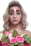 Portrait of a beautiful girl in a spring image on a white backgr. Ound, with creative make-up and a bouquet of flowers Stock Photo