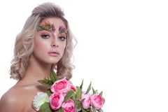 Portrait of a beautiful girl in a spring image on a white backgr. Ound, with creative make-up and a bouquet of flowers Royalty Free Stock Photography