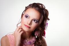 Portrait of beautiful girl with spring makeup and decoration tec. Portrait of curly brunette with purple make-up in pink dress with soutache technique Royalty Free Stock Images
