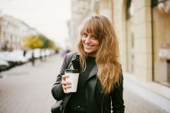Portrait of a beautiful girl on the street, holding a paper cup stock photography