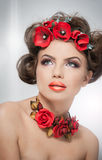 Portrait of beautiful girl in studio with red flowers in her hair and red roses around her neck. Young woman with makeup. And bright flowers as accessories stock photo