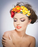 Portrait of beautiful girl in studio with red and yellow roses in her hair and naked shoulders. Sexy young woman with makeup Stock Image