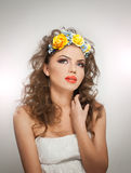 Portrait of beautiful girl in studio with yellow roses in her hair and naked shoulders. Sexy young woman with professional makeup Royalty Free Stock Photography