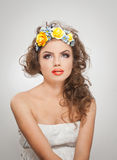 Portrait of beautiful girl in studio with yellow roses in her hair and naked shoulders. young woman with professional makeup Royalty Free Stock Images