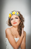 Portrait of beautiful girl in studio with yellow roses in her hair and naked shoulders. Sexy young woman with professional makeup Stock Image