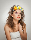 Portrait of beautiful girl in studio with yellow roses in her hair and naked shoulders. Sexy young woman with professional makeup Royalty Free Stock Images
