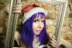 Portrait of beautiful girl in suit Santa Claus who holds baguette Royalty Free Stock Image