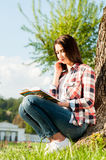 Portrait of beautiful girl in summer park reading a book Stock Photos
