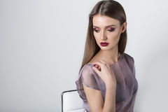 Portrait of a beautiful girl with a sweet delicate burgundy lips and bright makeup in a light transparent negligee studio on a whi. Te background Royalty Free Stock Photography