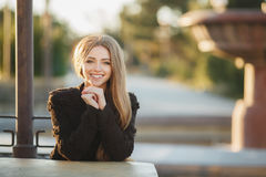 Portrait of a beautiful girl at a table in the street cafe. Young,beautiful,attractive woman,brunette with long straight hair and gray eyes,a beautiful smile and Stock Images