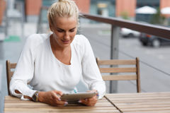 Portrait of a beautiful girl at the table with tablet Stock Photography