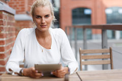 Portrait of a beautiful girl at the table with tablet Royalty Free Stock Photo