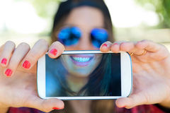 Portrait of beautiful girl taking a selfie with mobile phone. Stock Photography