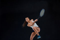 Portrait of beautiful girl tennis player with a racket on dark background Royalty Free Stock Photography