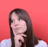 Portrait of beautiful girl thinking against red background Royalty Free Stock Images