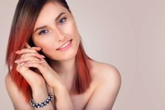 Portrait of a beautiful girl with tinted red hair. Portrait of a beautiful young smiling woman with tinted red hair Stock Photos