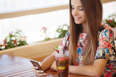 Portrait of beautiful girl using her mobile phone in cafe. Stock Photo