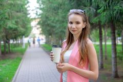 Portrait of beautiful girl walking on the park. Keeping takeaway drink in one hand. stock image